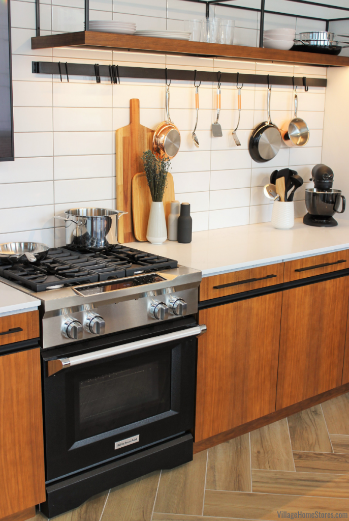 Matte black KitchenAid gas range in Imperial Black finish installed in an on trend kitchen with open shelves and copper accents.