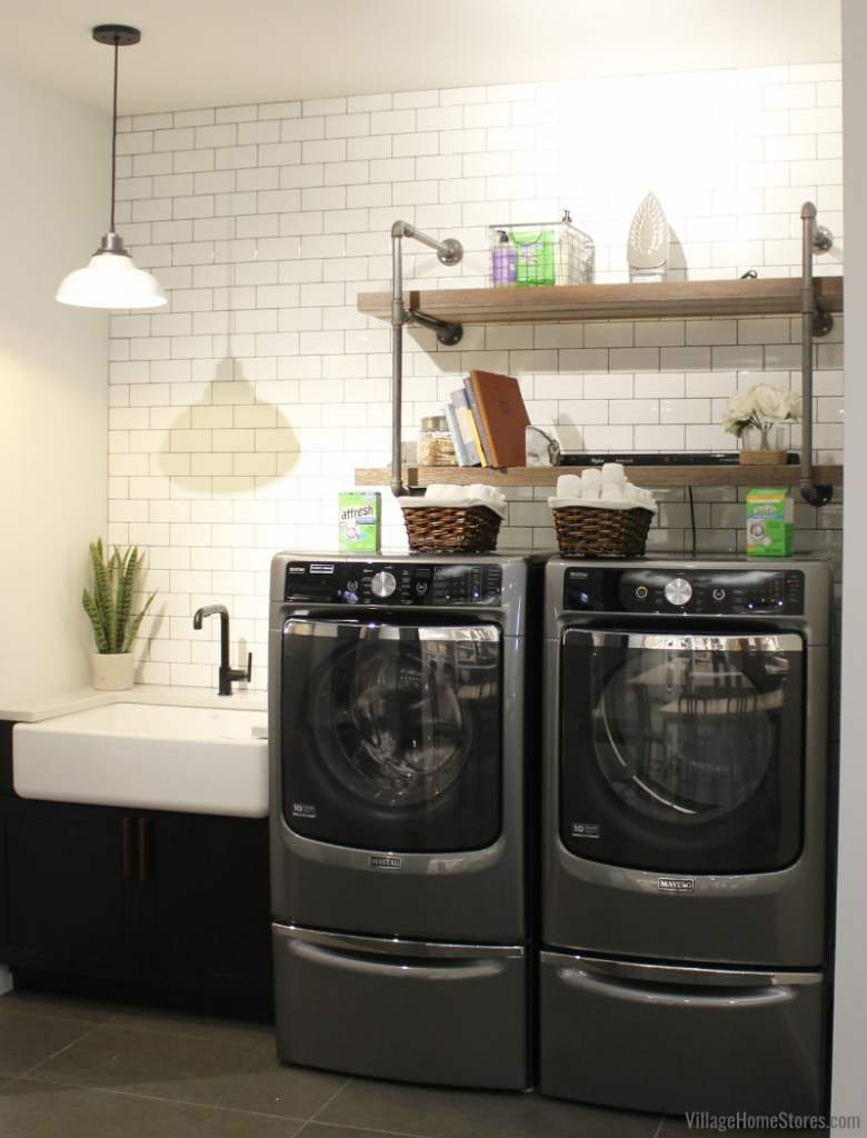 Maytag front-load laundry pair on pedestals installed in a farmhouse inspired laundry room with subway tile and a farm sink