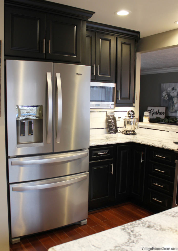 Black painted kitchen cabinetry with Stainless Appliances and Cambria Quartz in the Seagrove design. Kitchen design by Angela Weisbrod and complete kitchen remodel from start to finish by Village Home Stores.