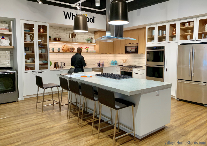 White and black kitchen with Sunset Bronze appliances in the World of Whirlpool experience center in Chicago, IL