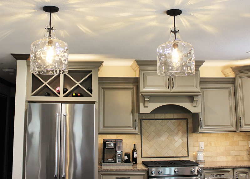 Capital pendant lighting with clear glass above a kitchen island. Kitchen remodel in Kewanee, IL with design and material by Village Home Stores.