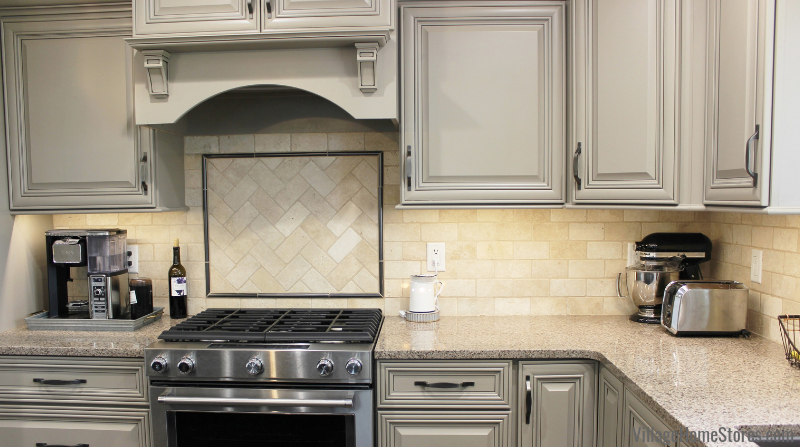 Farmhouse kitchen design in Kewanee, IL with wall tile and accent above cooktop by Village Home Stores.
