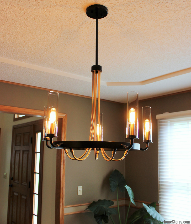 Black and gold Kearney Chandelier light from Savoy House hanging in a Bluegrass, Iowa formal dining room. Lighting by Village Home Stores.