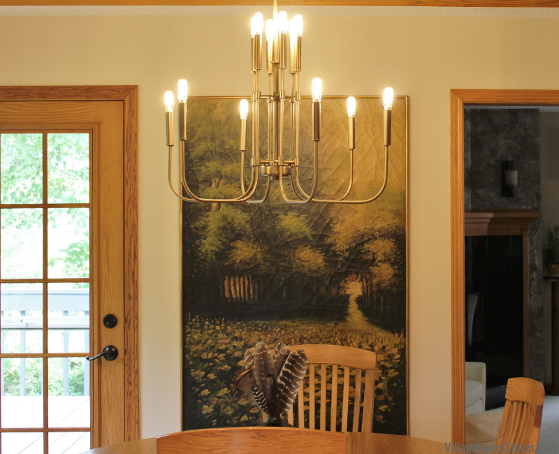Aged brass Zander Chandelier light from Capital Lighting hanging in a Bluegrass, Iowa dining space. Lighting by Village Home Stores.