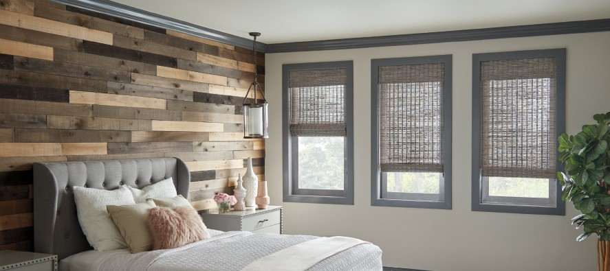Barnwood accent wall in bedroom with woven wood window shades.