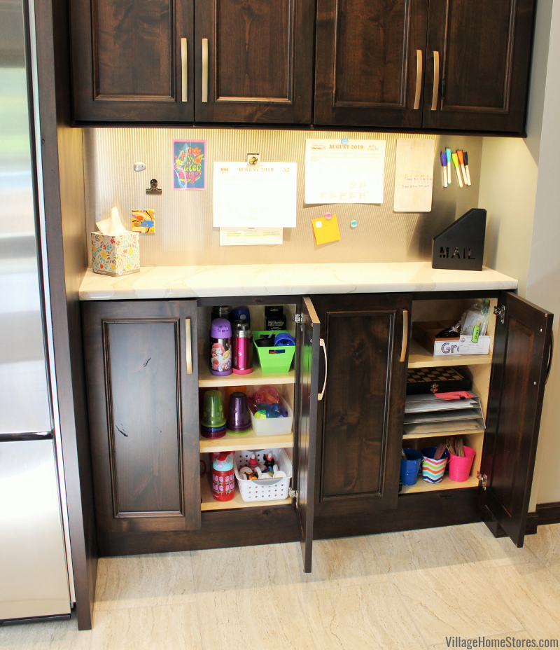Magnet wall kitchen dropzone for kids scheduling supplies and water bottles. Kitchen cabinetry, counters, appliances, and surfaces by Village Home Stores.