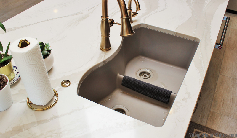 Low divider Gray undermount kitchen sink with Delta faucet in Cambria Brittanicca Warm quartz counters.