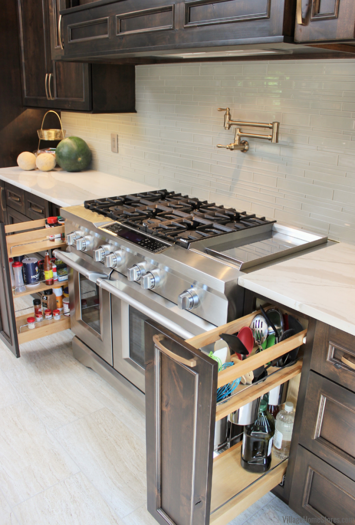Pullout storage cabinets surround a large KitchenAid range in a Quad Cities area kitchen.