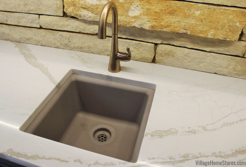 Undermount bar sink with Delta faucet in Cambria Brittanicca Warm quartz counters.