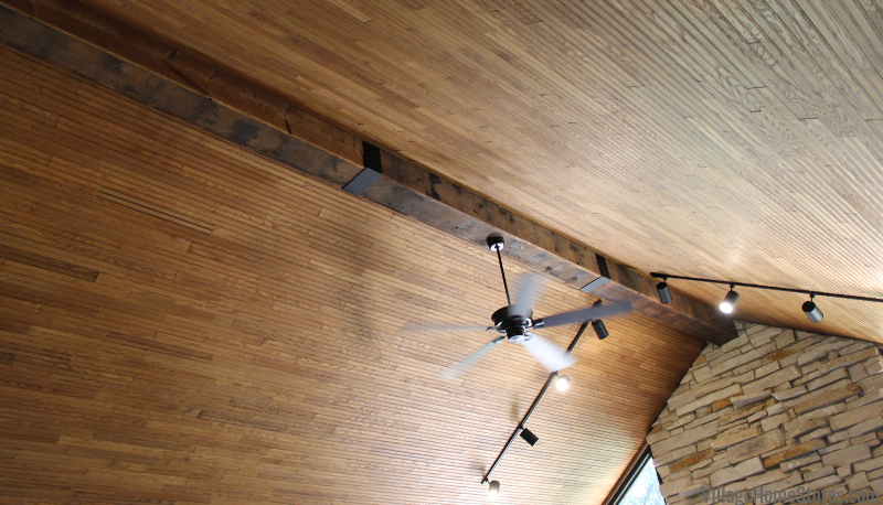 Barnwood wrapped beam wit iron brackets and new Quorum ceiling fan. Start to finish home remodel by Village Home Stores.