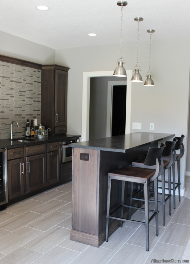 Bettendorf Quad Cities home bar with Stone stained Hickory cabinetry, Black Pearl brushed granite, Stainless appliances, pendant lights, and glass tile backsplash.