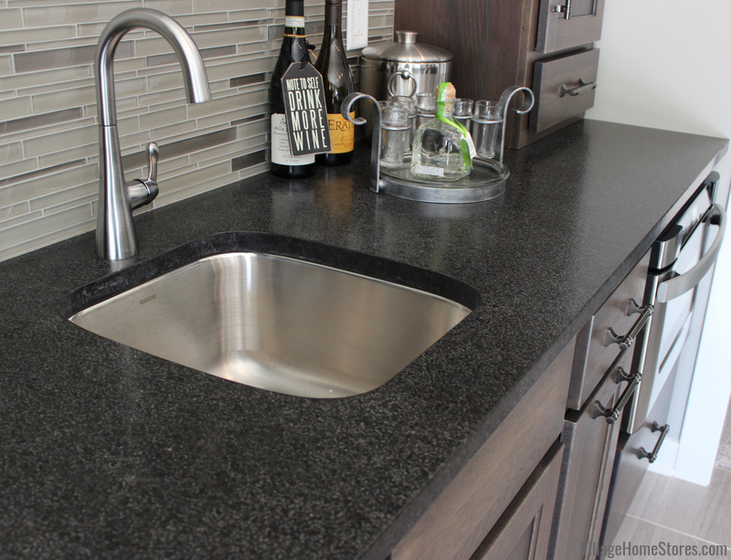 Stainless undermount bar sink installed in Black Pearl Brushed Granite countertops. Design and materials by Village Home Stores.
