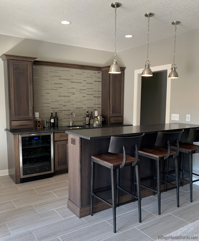 Bettendorf Quad Cities home bar with Stone stained Hickory cabinetry, black pearl brushed granite, pendant lighting, and glass tile backsplash.