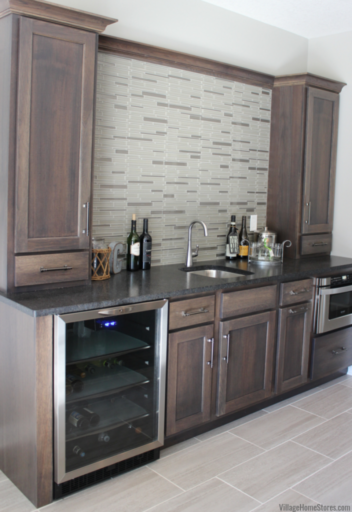 Bettendorf Quad Cities home bar with Stone stained Hickory cabinetry, Black Pearl brushed granite, Stainless appliances, and glass tile backsplash.