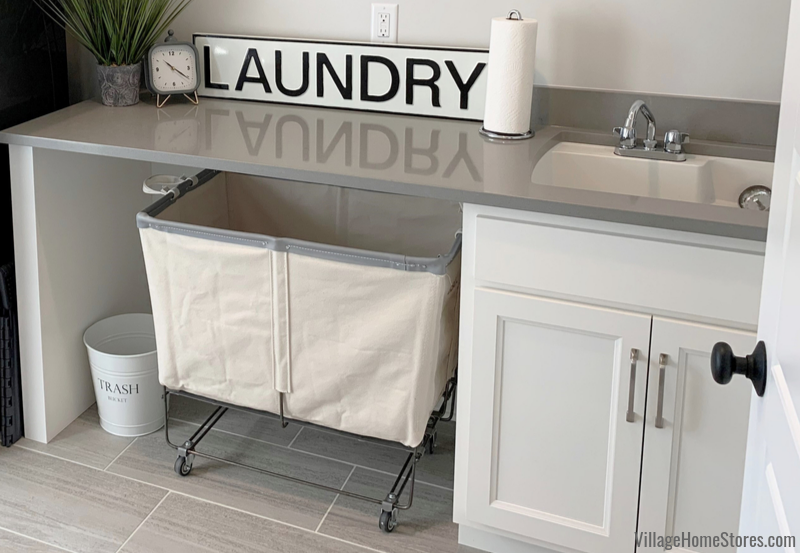 Laundry room with quartz counters and rolling laundry bin cart.