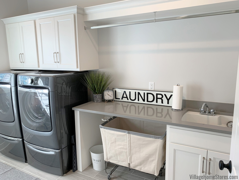Laundry room cabinets with quartz counters and front load Maytag Laundry.