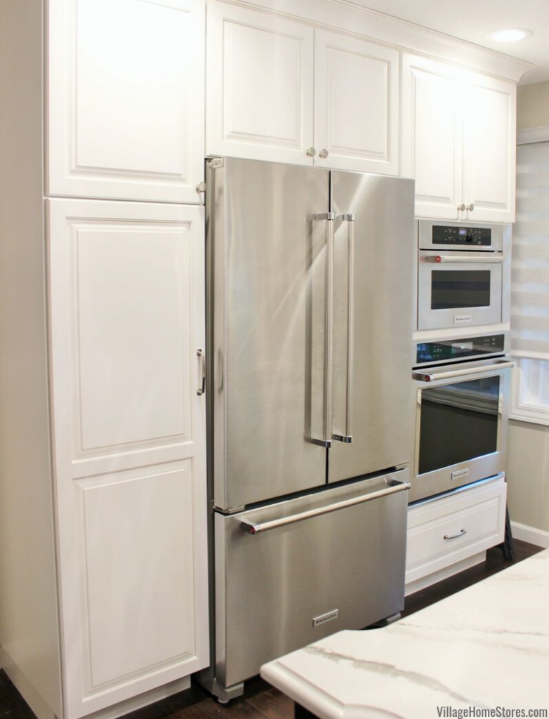 White pantry cabinet, counter depth refrigerator, and built-in wall ovens in a Bettendorf Iowa kitchen.