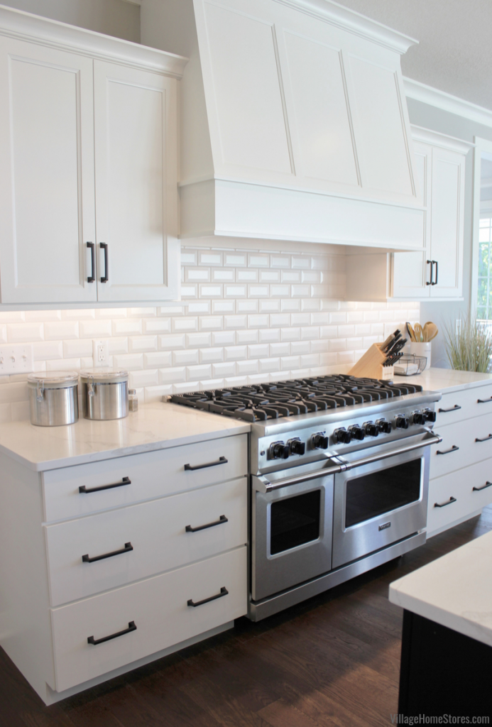 Custom white wood range hood and Viking gas range installed in a Bettendorf, Iowa kitchen.