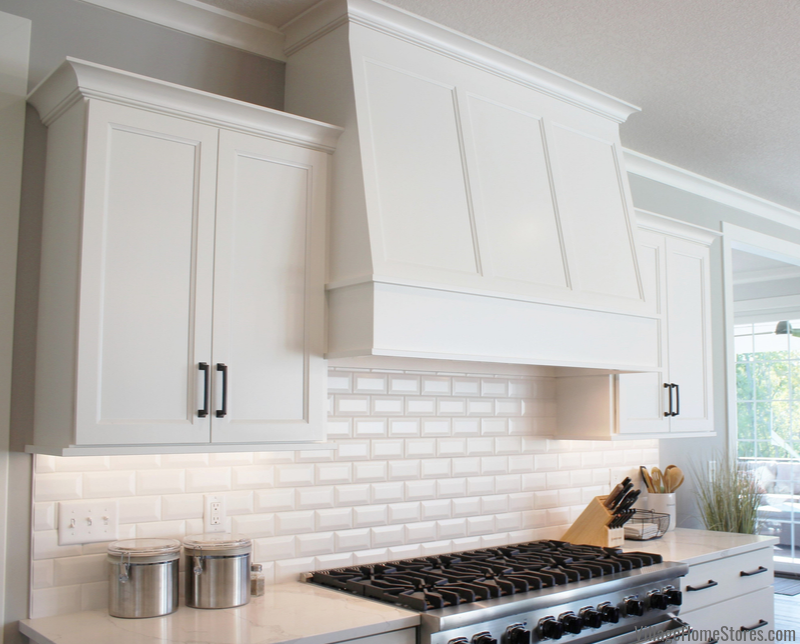 Custom wood range hood and beveled white subway backsplash tiles installed in a Bettendorf, Iowa kitchen.