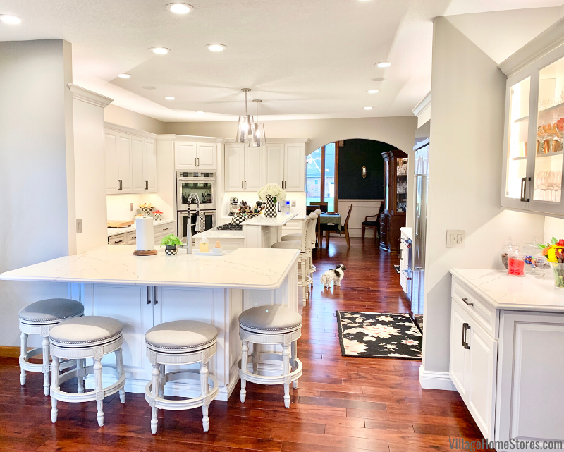 U shaped kitchen with white cabinets, quartz counters and cherry floors. Peninsula and dual level island design.
