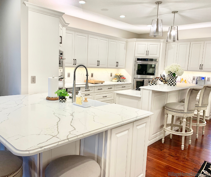 U shaped kitchen with white cabinets and cherry floors. Peninsula and dual level island design.