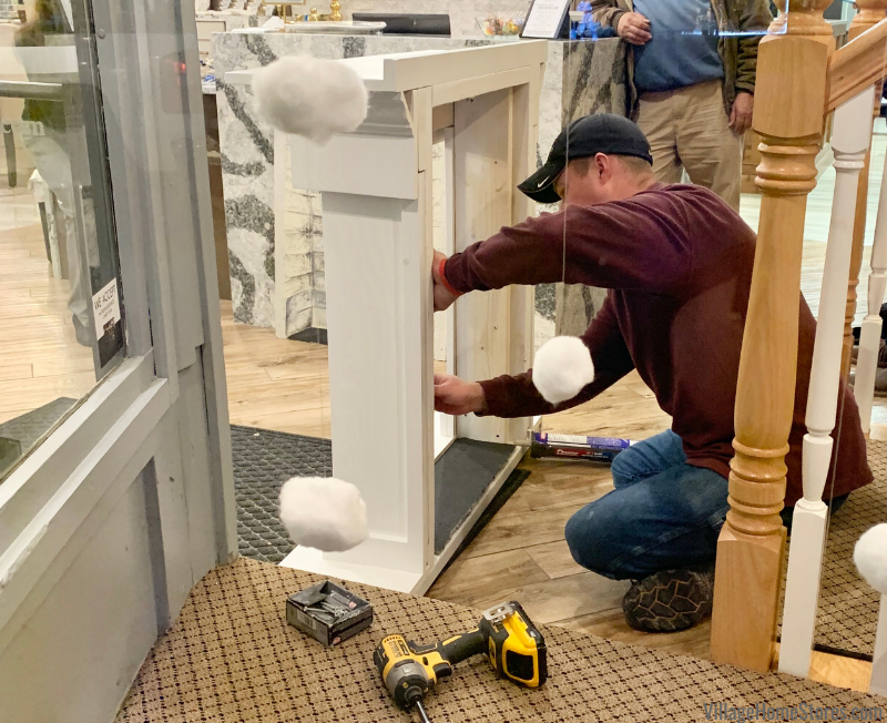 Scott Durian of Durian Builders puts the finishing touches on the faux fireplace he built for the Geneseo Giving Trees project.