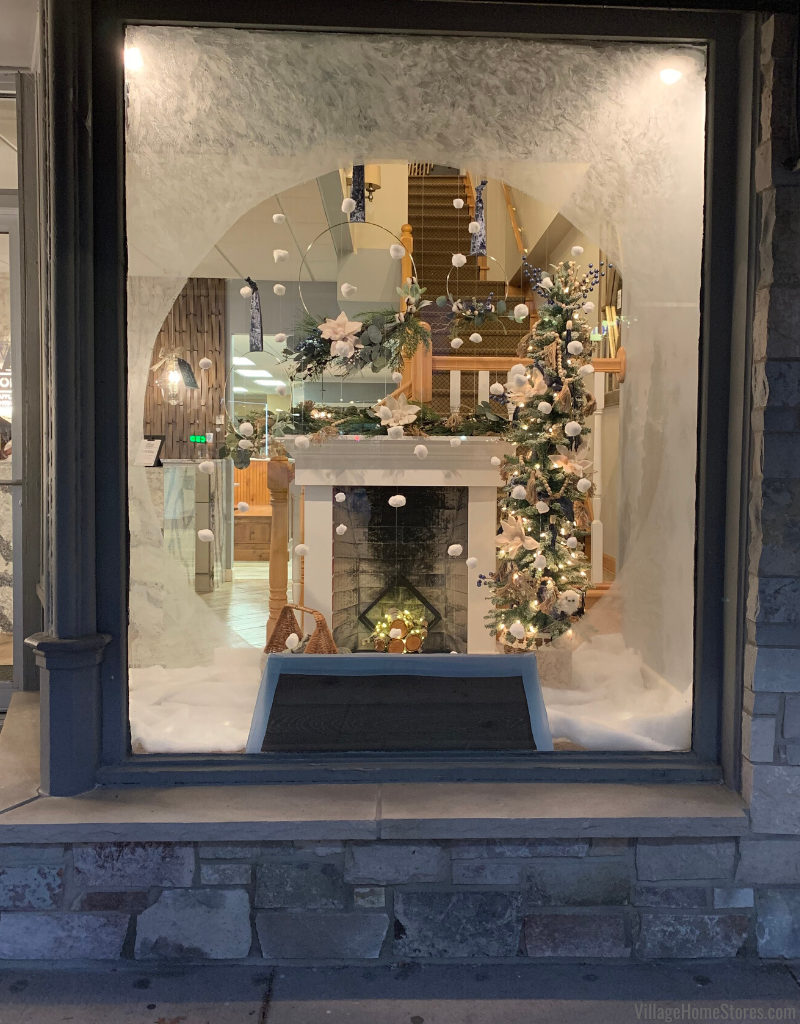 store window with snow globe look and fireplace and tree decor for holidays