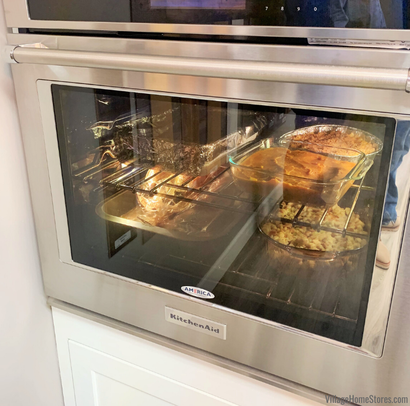 KitchenAid Stainless Steel wall oven with Thanksgiving side dishes inside.