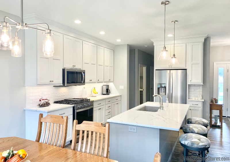Geneseo kitchen with Koch cabinetry, Kichler lighting, Whirlpool appliances, and Calacatta Laza quartz countertops. Kitchen design and products from Village Home Stores for Bob Johnson Construction.