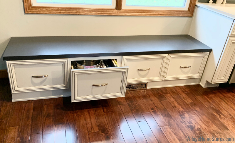 Kitchen bench with storage drawers below a dinette window. Kitchen design and complete remodel in Rock Island Quad Cities by Village Home Stores.