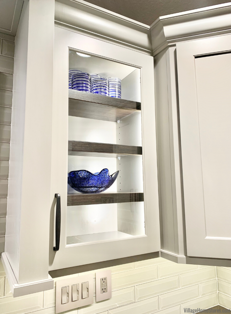 Lighted glass door cabinet in kitchen with contrasting interior shelves.