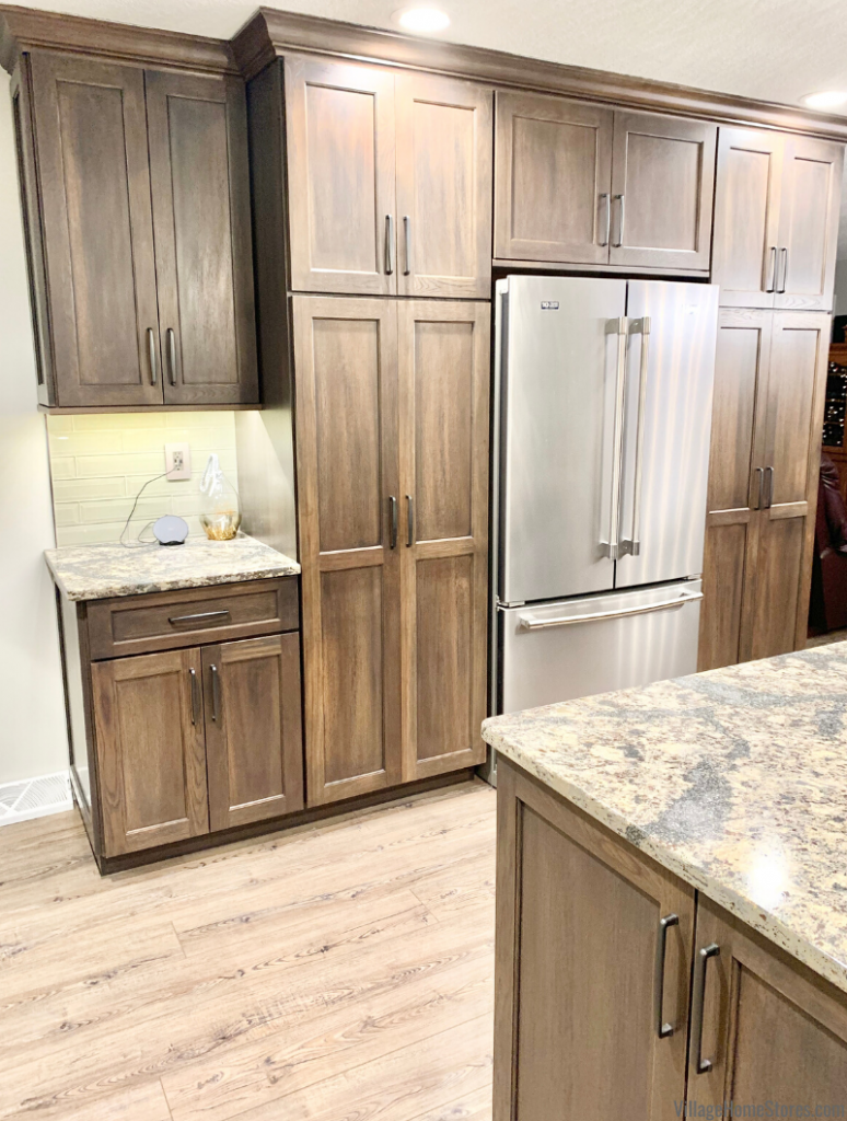 Gray stained tall pantry cabinets surround a refrigerator in a remodeled Morrison, IL kitchen. Kitchen design and remodel by Village Home Stores.