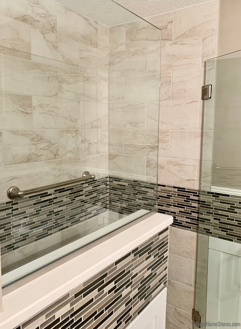 Custom tiled shower with glass wall tile accents and glass door installed in a remodeled Morrison, IL bathroom. Bathroom designed by Angela Weisbrod and remodeled by Village Homes Stores.