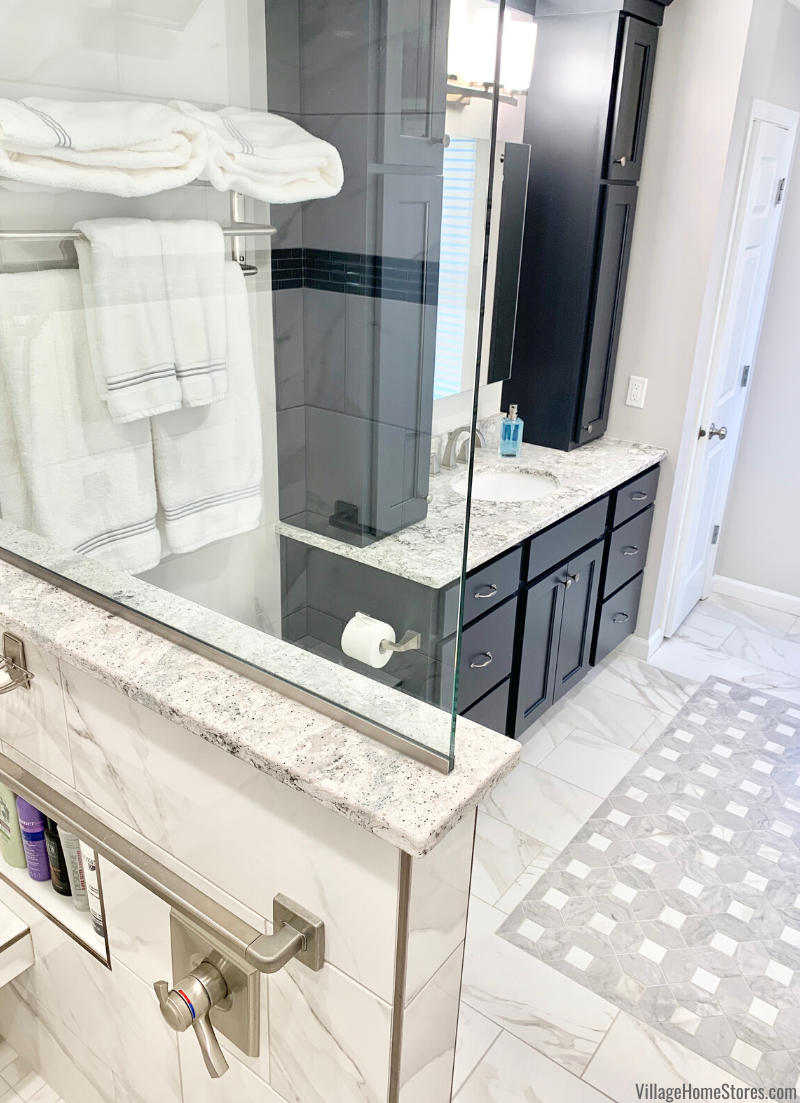 Custom tiled shower and inlay tile rug in a master bathroom with blue cabinets