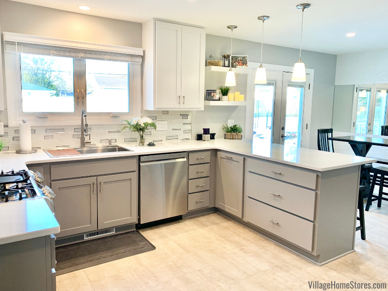 U shape kitchen with peninsula seating in Moline IL. Fog gray bases and white upper cabinets paired with Hanstone Quartz counters.