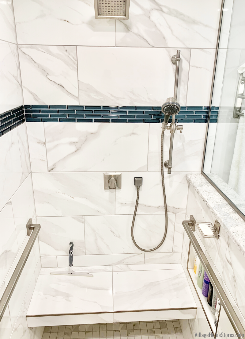 Custom tiled walk in shower with bench and niche shelf in a remodeled Bettendorf bathroom.