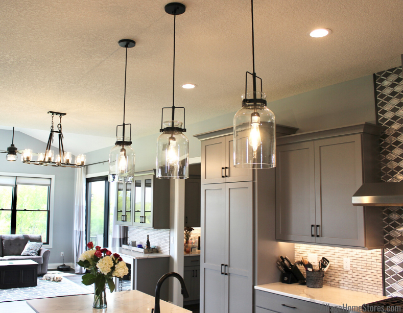 Three jar shaped pendant lights hang above kitchen island with dinette light and fan within view. Lighting and kitchen by Village Home Stores