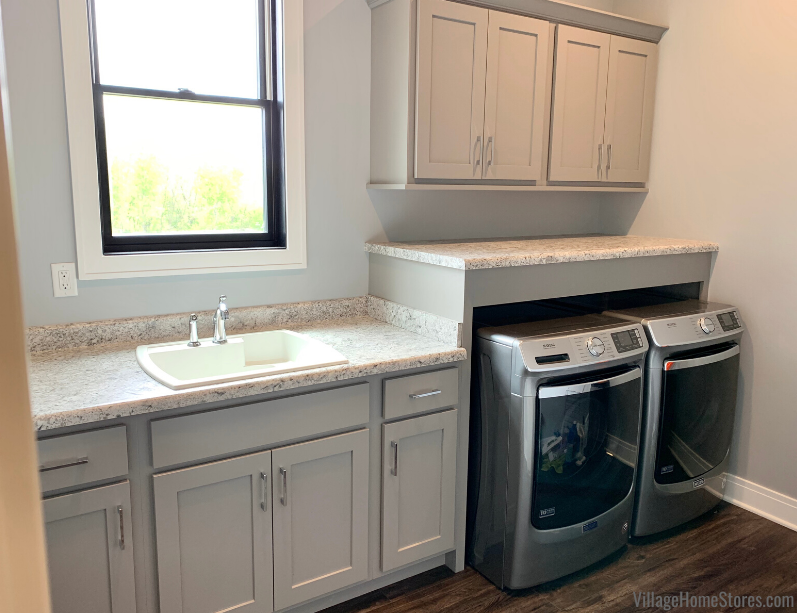 Koch Express cabinetry and Maytag front load laundry in a Bettendorf Quad Cities laundry room. Design and materials from Village Home Stores