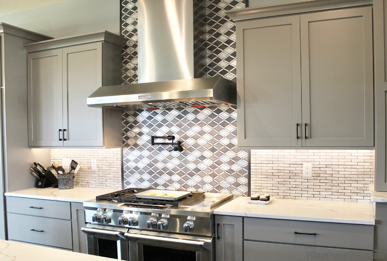 Metal mosaic wall tile above cooktop in kitchen with large range and stainless steel hood