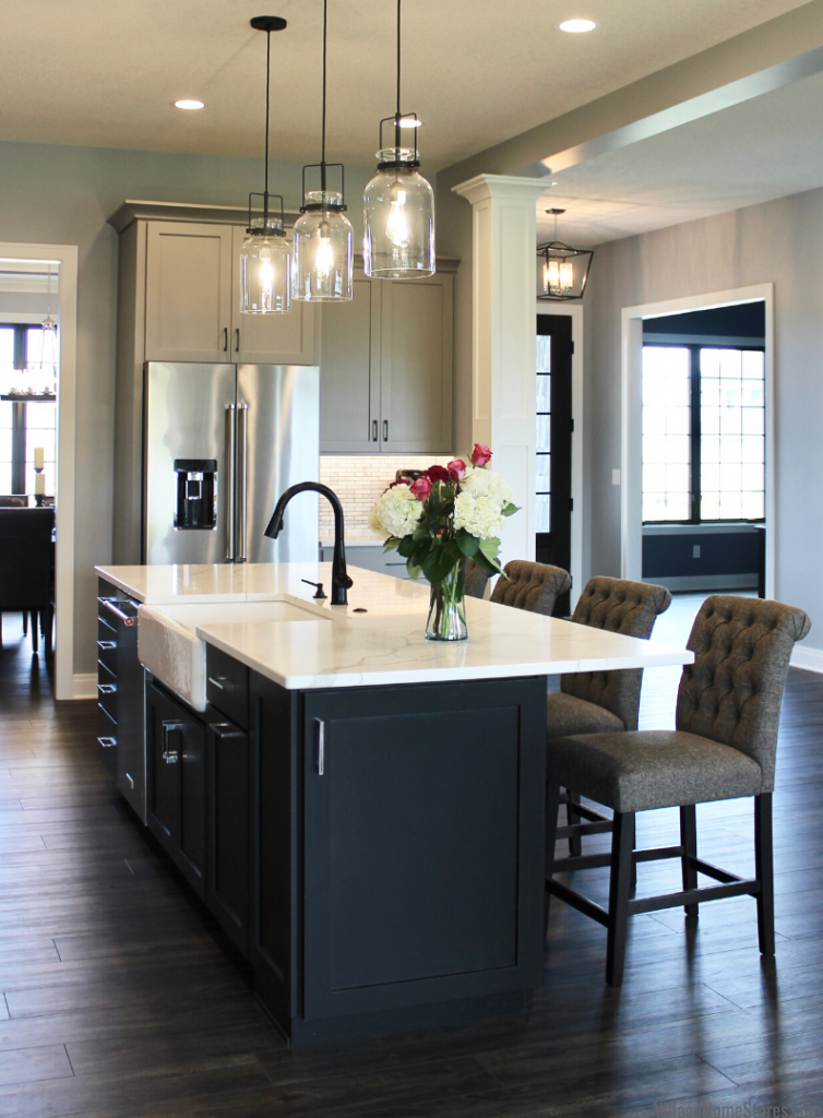 Jar shaped pendant lights above kitchen island in Bettendorf Iowa. Lighting and kitchen by Village Home Stores