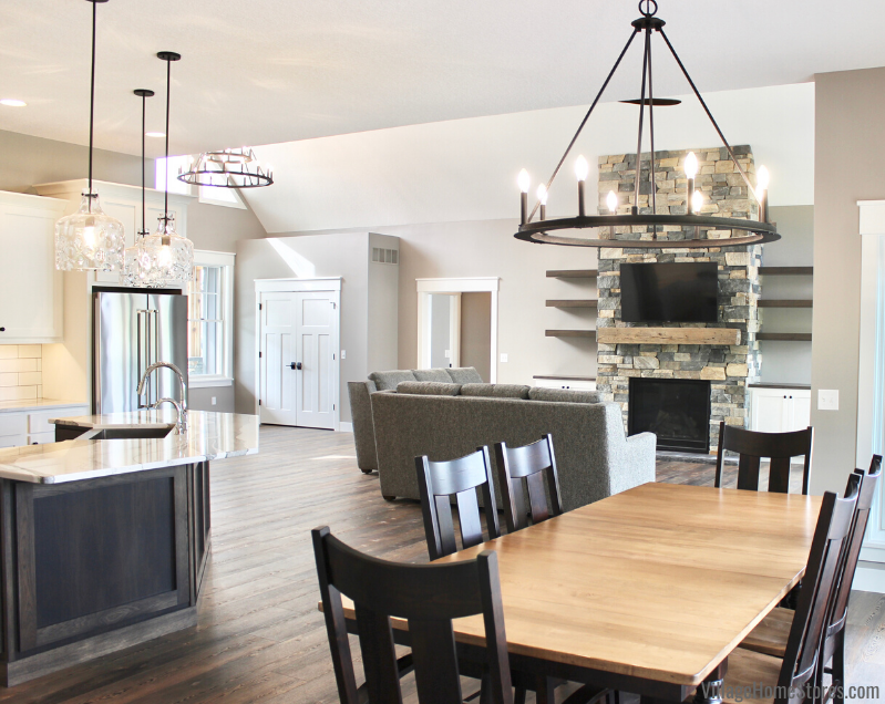 Farmhouse style lighting. Pearson chandelier and clear water glass pendants above kitchen island in a new home in Aledo, IL. Lighting by Village Home Stores for Bagby Construction