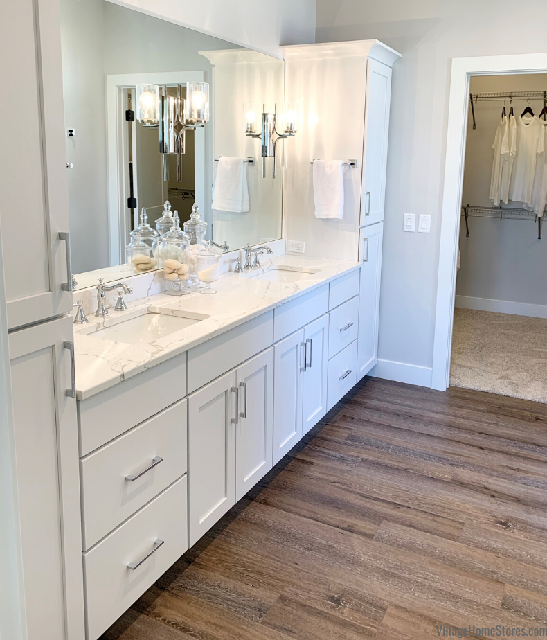 Principal bathroom design with two sinks, white cabinets, vanity lights on mirrors, and Quartz counters.