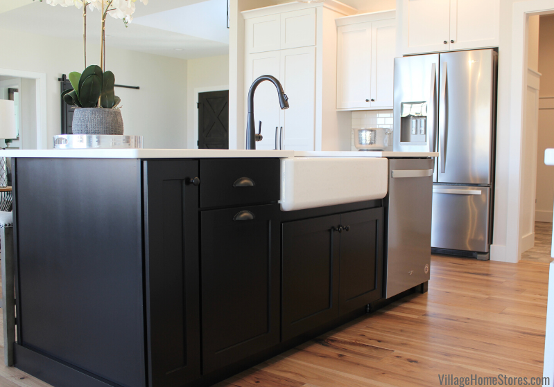 Black painted kitchen island with farm sink and stainless steel dishwasher