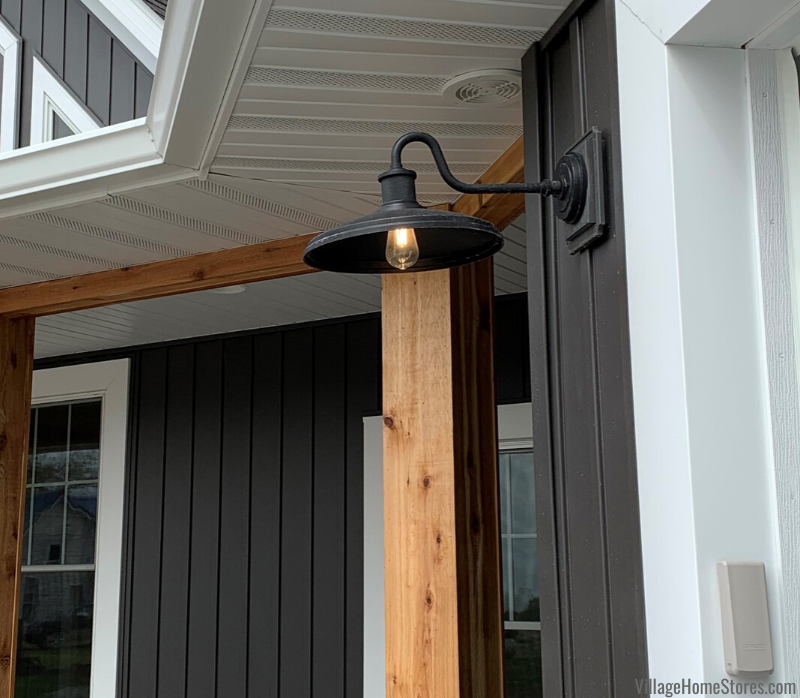 Matte black arm light on garage door of farmhouse. Exterior lighting from Village Home Stores.