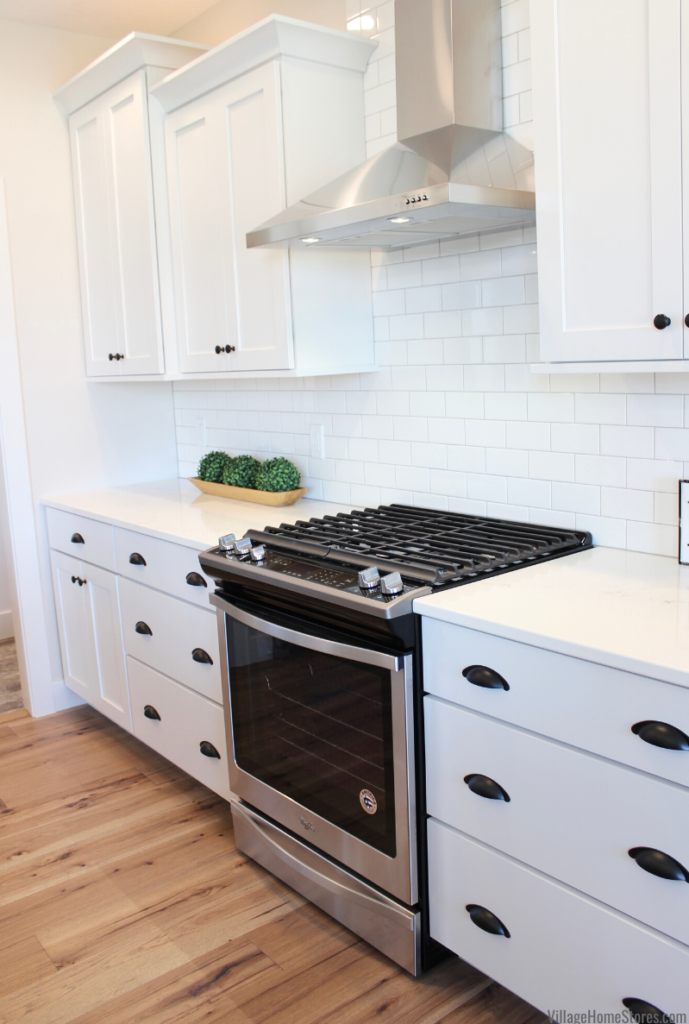 Stainless Steel gas range and chimney style hood in white painted Bettendorf Iowa kitchen.