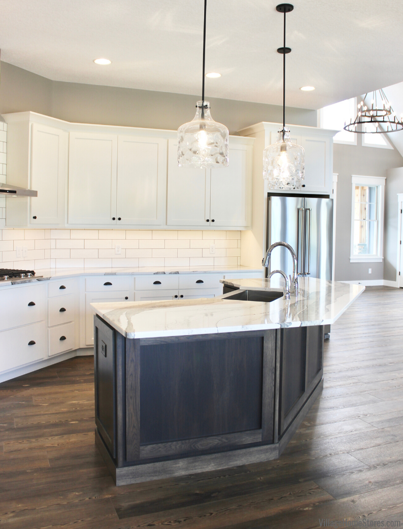 Kitchen design with angled gray stained island, Skara Brae Cambria tops, and glass pendants.
