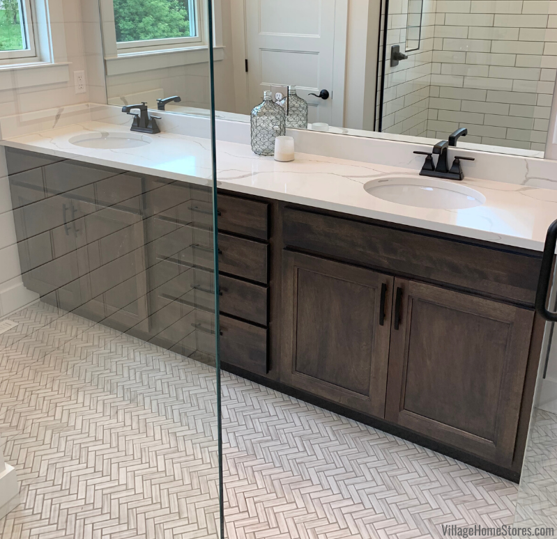 Primary bathroom cabinets with two sink layout and storage at the center. Cabinetry by Village Home Stores for Applestone Homes.