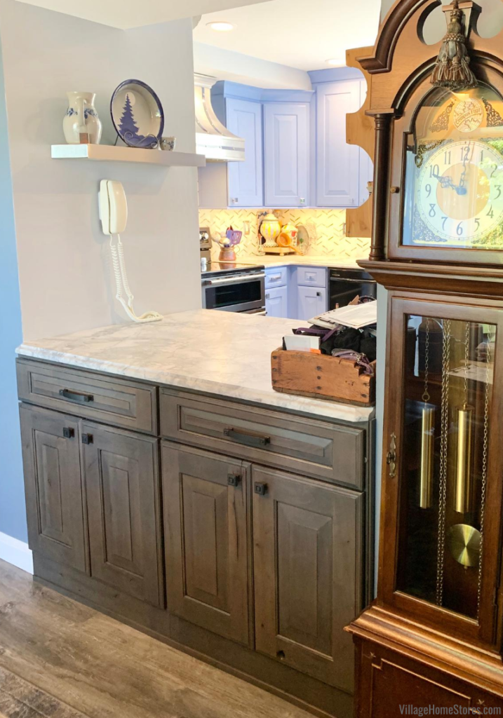 Rustic Alder cabinets in a warm gray stain installed underneath a pass through area from kitchen to dining room.
