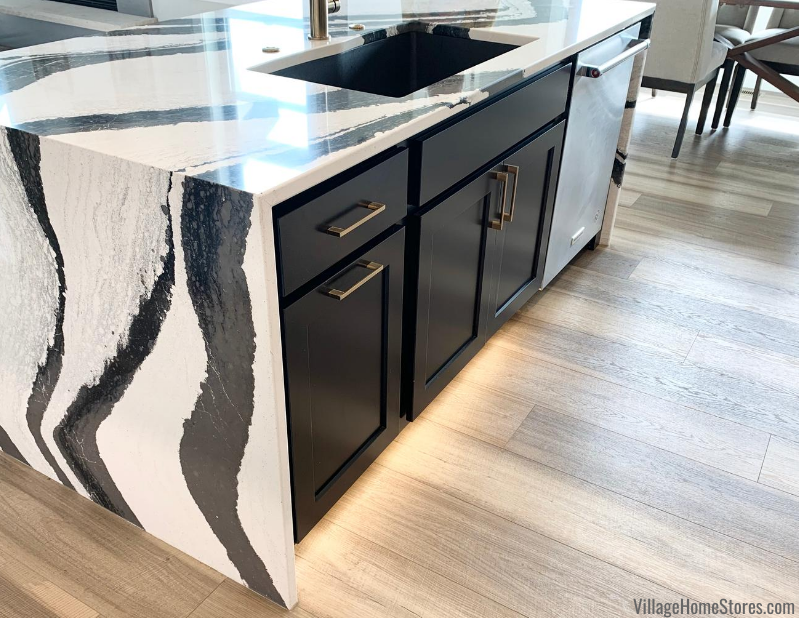 Kitchen island in Savannah Koch Cabinet door painted Black finish. Waterfall Cambria counters and toekick lighting also featured.