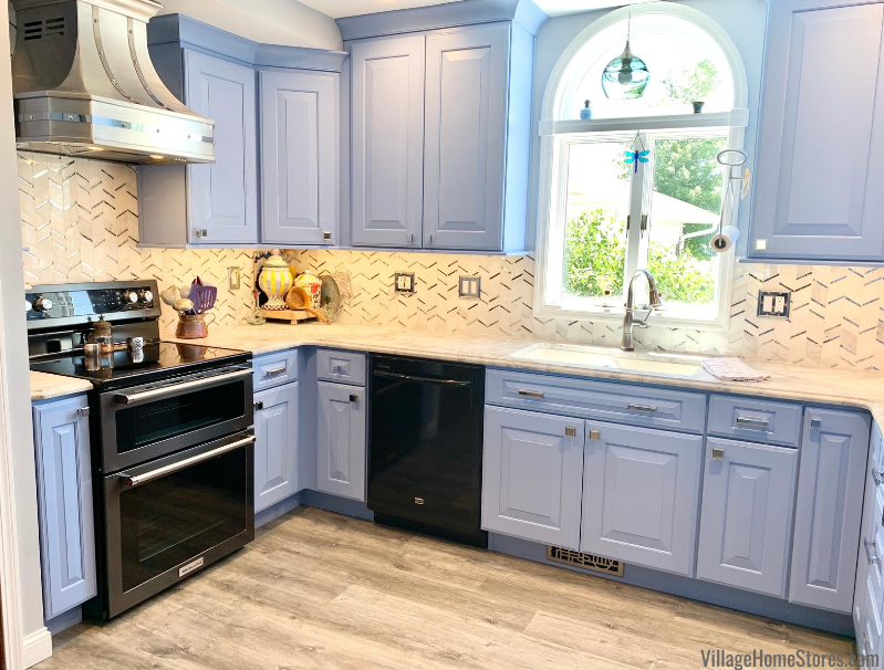 Blue cabinet kitchen with matte white marble counters and a mirror and marble backsplash. Design, materials, and complete remodel from Village Home Stores.